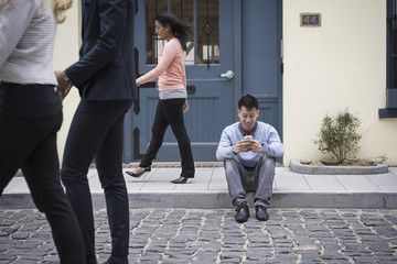 Young people outdoors on the city streets in springtime. A man sitting on the ground checking his phone, and three passers-by.