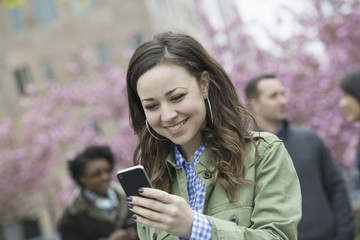 A young woman checking her smart phone for messages in the park. A group of friends in the background.