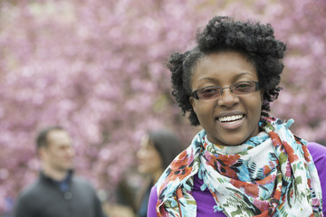 A group of people under the cherry blossom trees in the park. A young woman smiling and looking at the camera. Wearing a floral scarf.