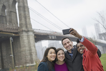 New York city. The Brooklyn Bridge crossing over the East River. Four friends taking a picture with a phone, a selfy of themselves.