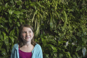 Outdoors in the city in spring. An urban lifestyle. A young girl standing in front of a wall covered with ferns and climbing plants.
