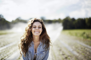 A young woman in denim jacket standing in a field, irrigation sprinklers working in the background.