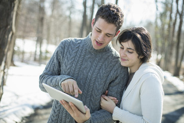 A couple looking at a computer tablet. Standing close together on a winter day in the woods.