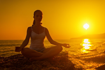 Fototapete - woman meditating in lotus pose on the beach at sunset