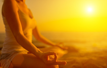 Wall Mural - hand of  woman meditating in a yoga pose on beach at sunset