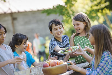 A group of children around a table, eating fresh fruitss and salads.