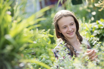 Summer on an organic farm. A young girl in a plant nursery full of flowers.