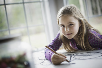 A family home.  A child sitting at a table using a pencil and creating a line drawing. Artwork. Drawing.