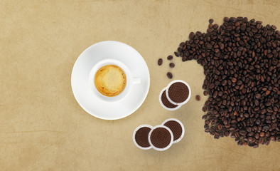 cup of coffee with beans, coffee pods on marble table