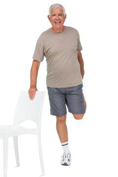 Full length portrait of a happy senior man stretching leg