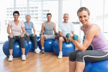 Fitness class with dumbbells sitting on exercise balls