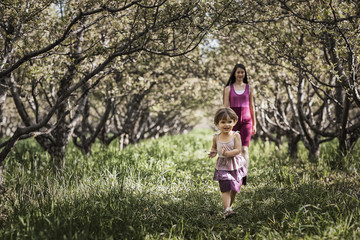 Two children walking in a woodland tunnel of overarching tree branches.