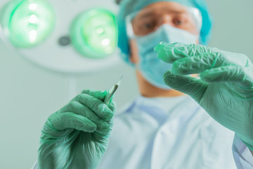 Male surgeon holds a scalpel