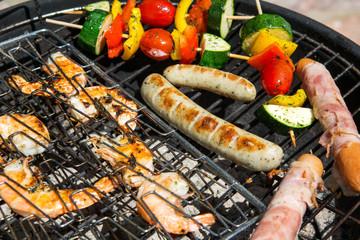 Sausages, big prawns and vegetable skewers smoking on grill