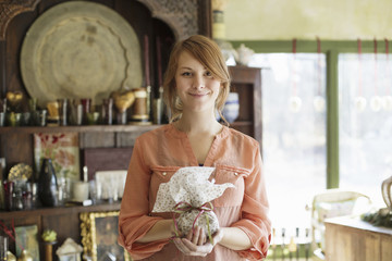 Young woman holding gift in antique store