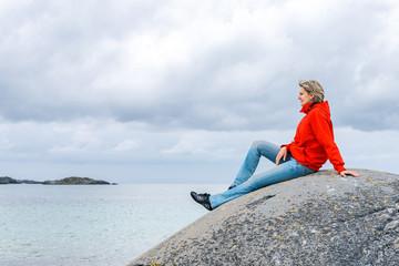 Woman sitting on stone and enjoying sea view