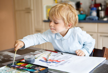 Adorable boy of two years drawing with paints.
