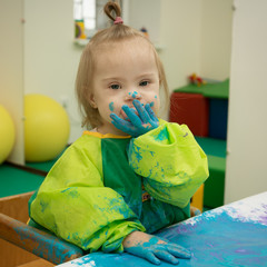 Girl with Down syndrome is busy painting