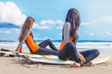 Surfer girls relaxing near the ocean