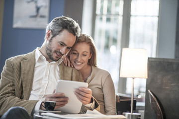 cheerful couple sitting in a cafe and using a digital tablet
