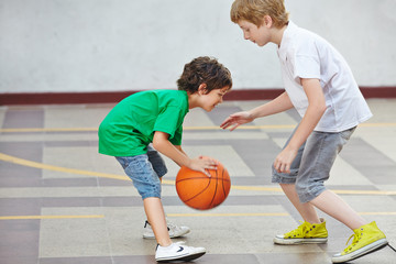 Boys playing basketball in school
