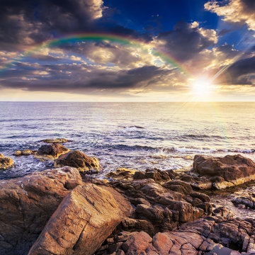 sea wave breaks about boulders at sunset with rainbow
