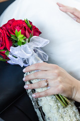 Hands of just married woman holding bouqet
