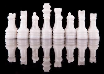 Stone made chess set on black background