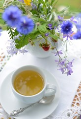 Сup of tea and a bouquet of flowers
