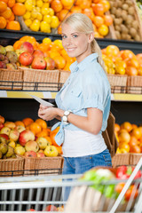 Girl looks through shopping list near the stack of fruits