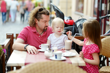 Father and his daughters relaxing in outdoor cafe