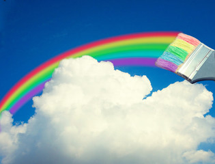 paint brush draws a rainbow in the sky
