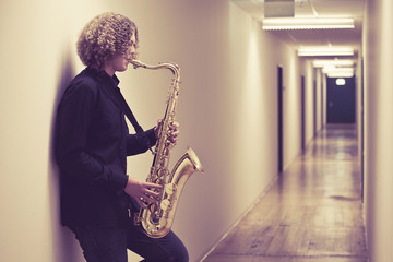 Man playing the saxophone in a hallway