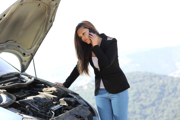 Woman on the phone looking her crash breakdown car