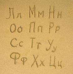 Russian alphabet (second part of three) written on a sand beach.