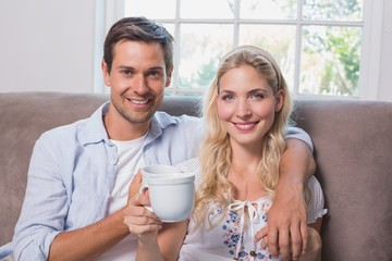 Portrait of a loving couple with coffee cups in living room