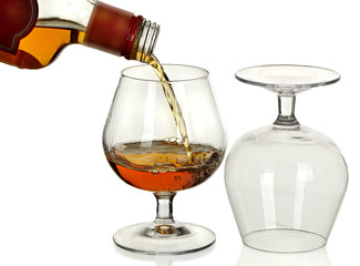 Bottle of brandy, a jet, and two wine glass isolated on a white
