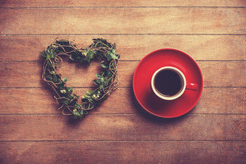 Cup of coffee and shape heart on a wooden table.