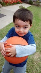Cute mixed-race boy playing with basketball outside.