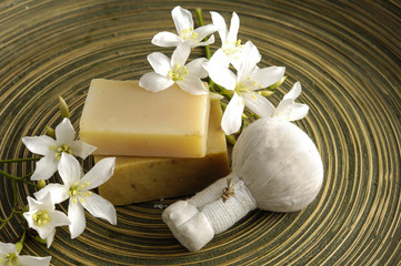 flower and soap with massage ball on wooden plate