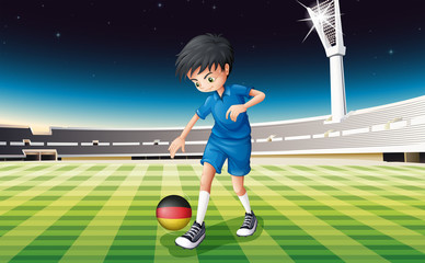 A boy at the field using the ball with the flag of Germany