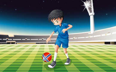 A boy at the field using the ball with the flag of Norway