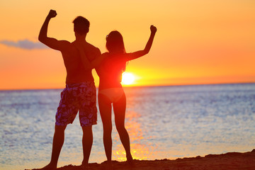 Sporty fitness couple cheering at beach sunset