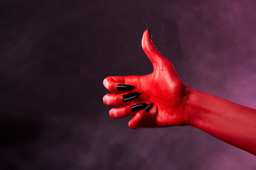 Red devil hand showing thumbs up