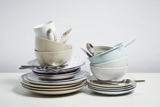 Dirty dishes pile needing washing up on white background