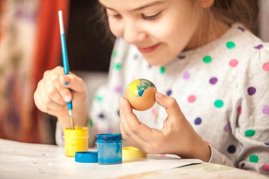 Happy little girl painting easter egg