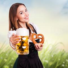 junge Frau im Dirndl mit Bier und Willkommensgruß