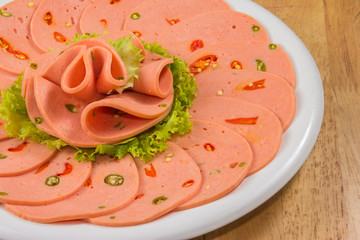 Spicy bologna in a white dish on wood tabletop
