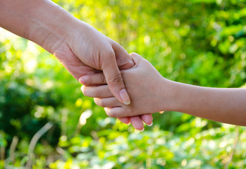 Hands of mother and daughter holding, Green park in background