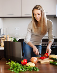 woman looking in notebook during cooking vegetables